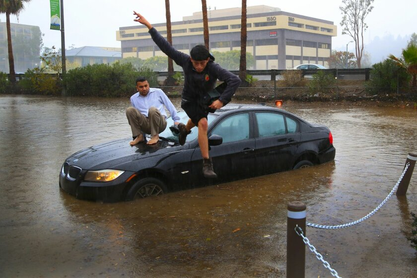 Octavio Angulo (jumping) and Mike Patel had to abandoned their vehicle on South Hotel Circle in Mission Valley Road when the flooded road stalled their vehicle's engine.