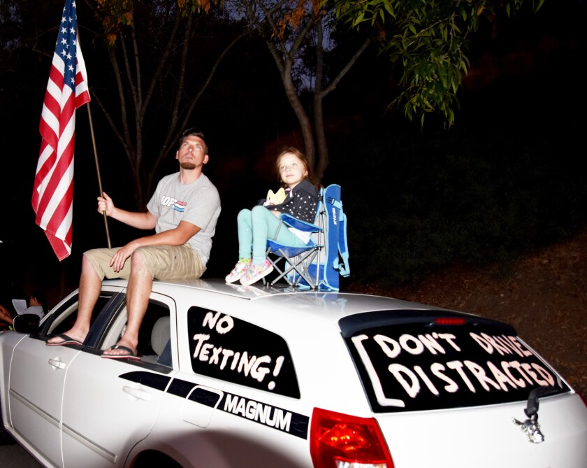 Johnny and Aurora Norriss sat on top of their vehicle to watch last year's fireworks show at Poway Sportsplex.