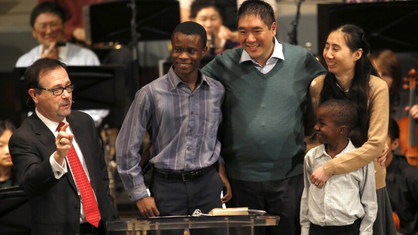 Pastor Greg Waybright, left, welcomes Matt and Grace Huang and their sons Immanuel, left, and Josiah on their return to the Lake Avenue Church in Pasadena on Sunday.