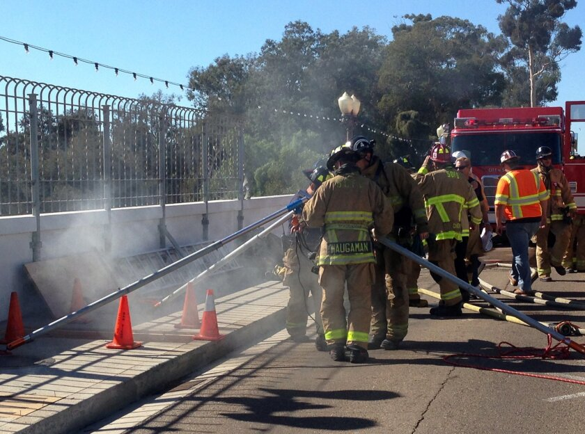 Firefighters work to put out a fire at the Cabrillo bridge that was sparked by a construction crew Thursday.