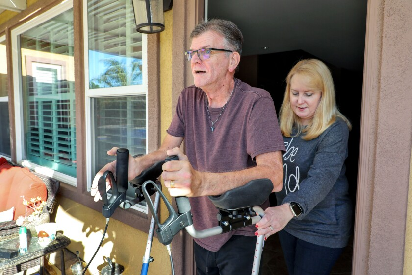 Navy veteran Bruce Courtney, who has ALS, gets assistance using his walker from his wife Lori, who teaches fourth grade.