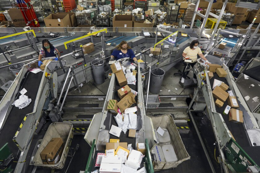 Employees work with an automated parcel and bundle sorter at the Postal Service center in the City of Industry.