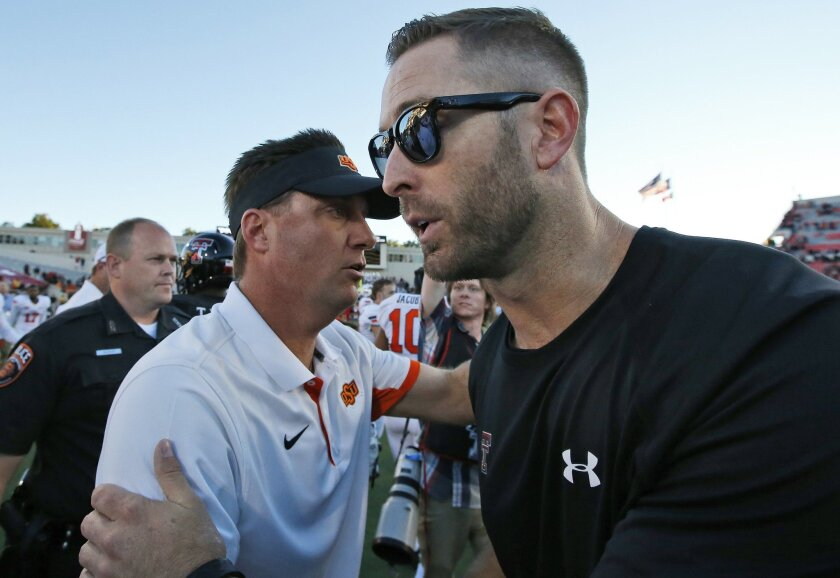 Oklahoma State head coach Mike Gundy, left, and Texas Tech head coach Kliff Kingsbury, right, meet at mid field after their NCAA college football game in Lubbock, Texas, Saturday, Oct. 31, 2015. Oklahoma State won 70-53. (AP Photo/Sue Ogrocki)