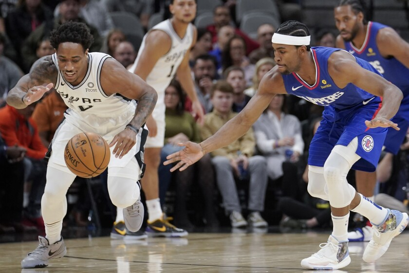 San Antonio Spurs forward DeMar DeRozan, left, and Clippers forward Maurice Harkless chase after a loose ball.