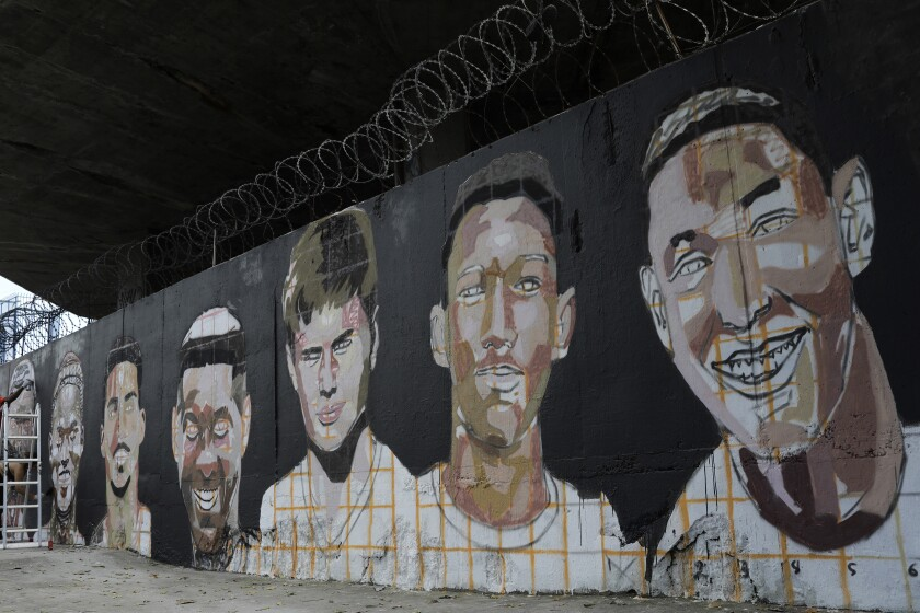 A mural features the faces of the young soccer players who died one year ago in a fire at the Flamengo club training center in Rio de Janeiro, Brazil, Friday, Feb. 7, 2020. The fire killed 10 academy players and injured three others, all aged between 14 and 16 years-old at the time. (AP Photo/Silvia Izquierdo)