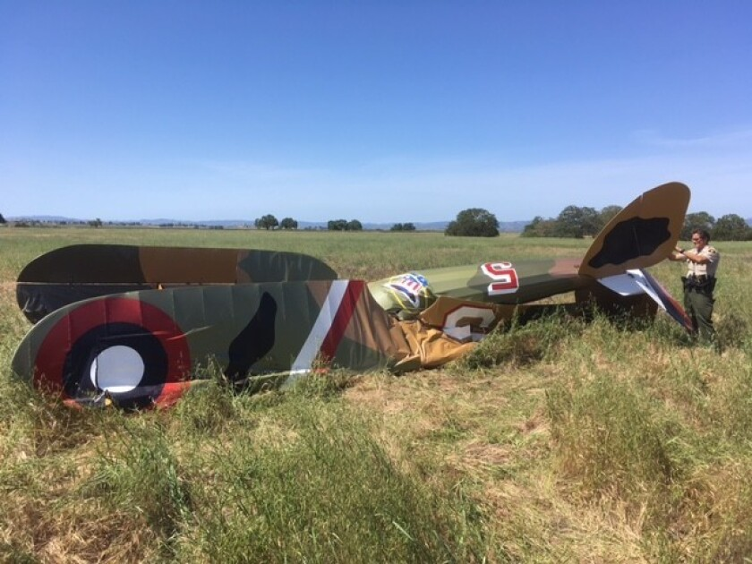 A sheriff's deputy inspects the wreckage of a World War I replica airplane that crashed in Paso Robl