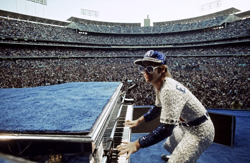 Elton John, dressed in a sequined baseball outfit, performs with the Dodger Stadium crowd behind him.