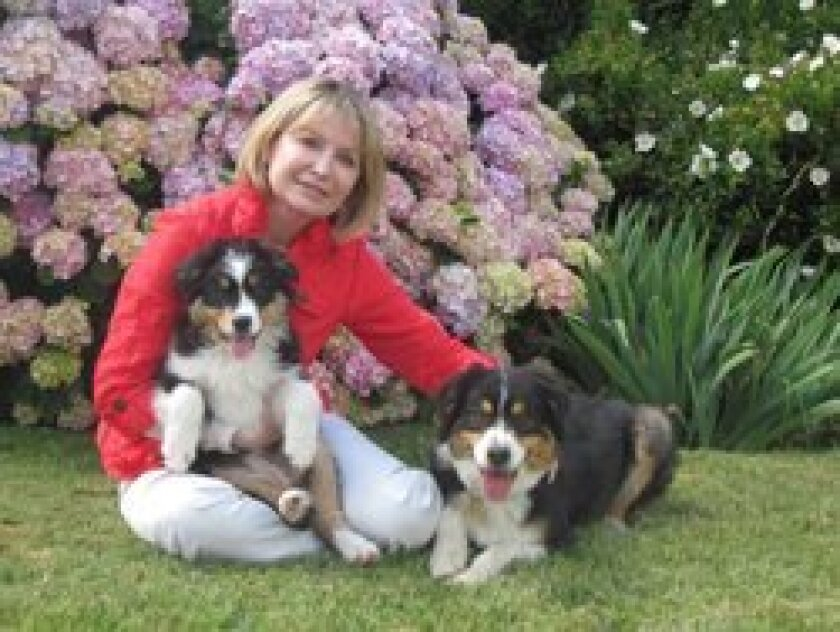 Susan Blick relaxes with Gracie, her new puppy, and Gracie's playmate Sophie.