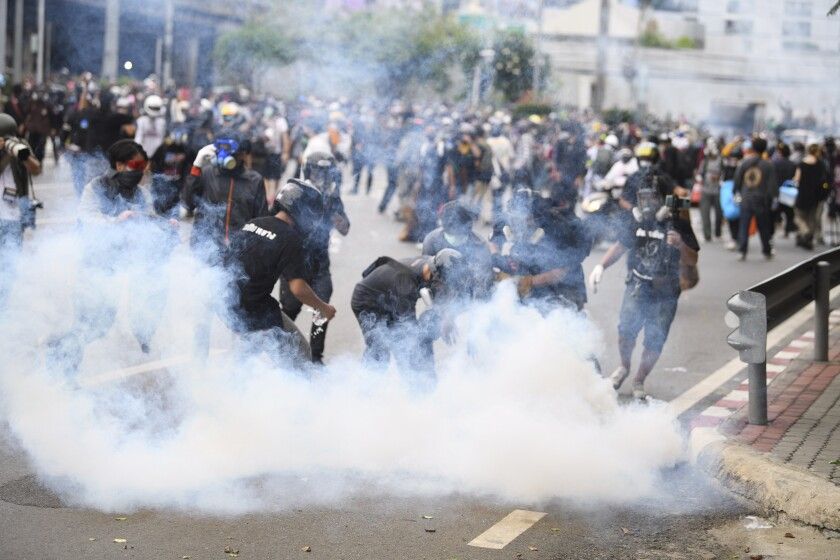 An anti-government protester tries to control smoke from a tear gas canister fired by riot police during a protest in Bangkok, Thailand, Friday, Aug. 13, 2021. Protesters demanded the resignation of Prime Minister Prayuth Chan-ocha for what they say is his failure in handling the COVID-19 pandemic.(AP Photo/Thanachote Thanawikran)