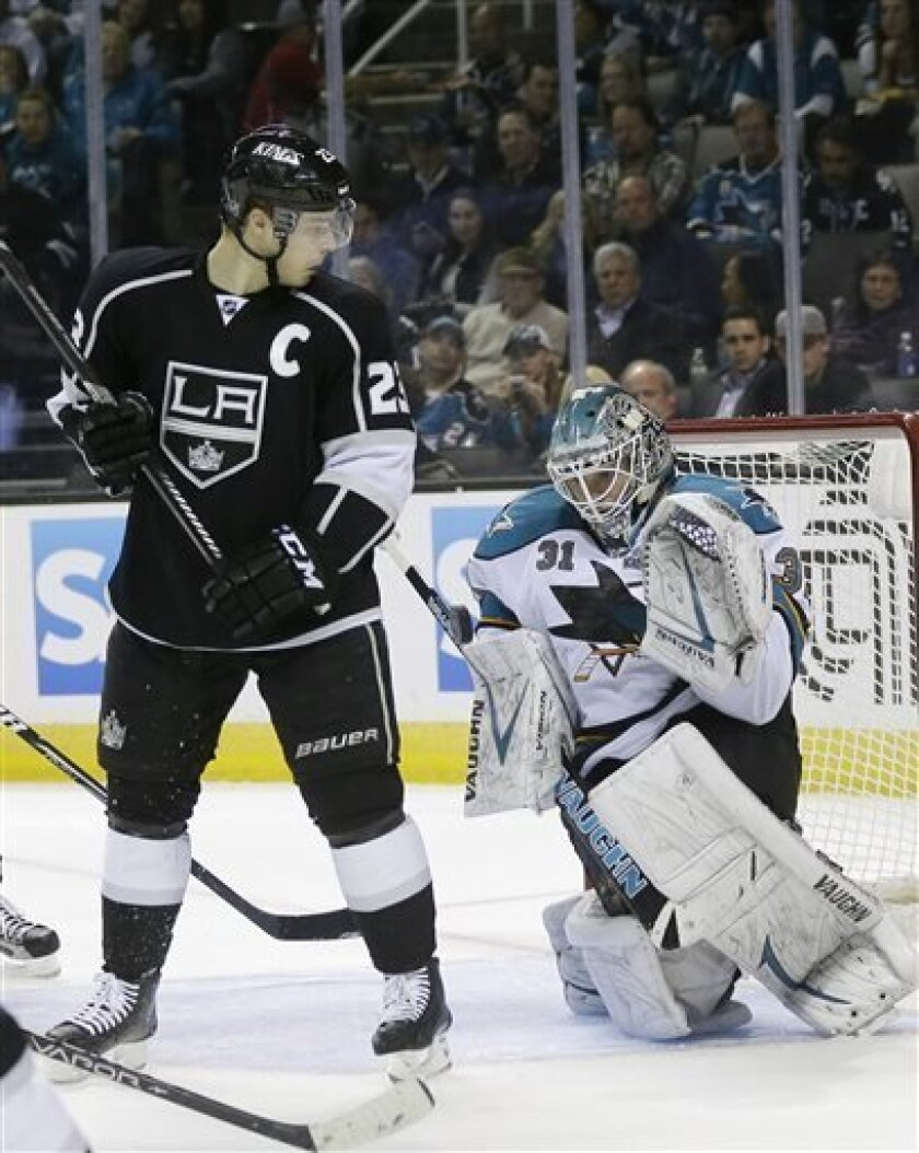 San Jose Sharks goalie Antti Niemi, of Finland, stops a shot next to Los Angeles Kings right wing Dustin Brown (23) during the second period of an NHL hockey game in San Jose, Calif., Tuesday, April 16, 2013. (AP Photo/Marcio Jose Sanchez)