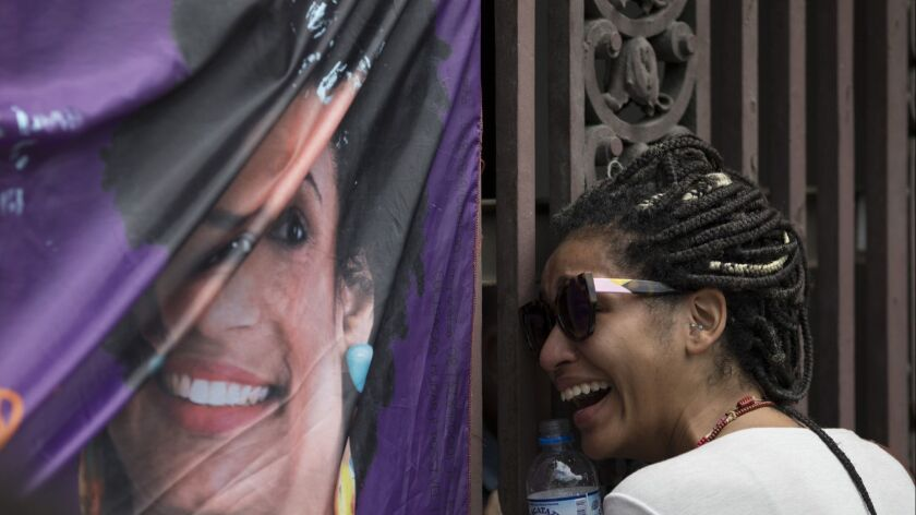 A woman cries next to a banner with an image of councilwoman Marielle Franco at the entrance of City