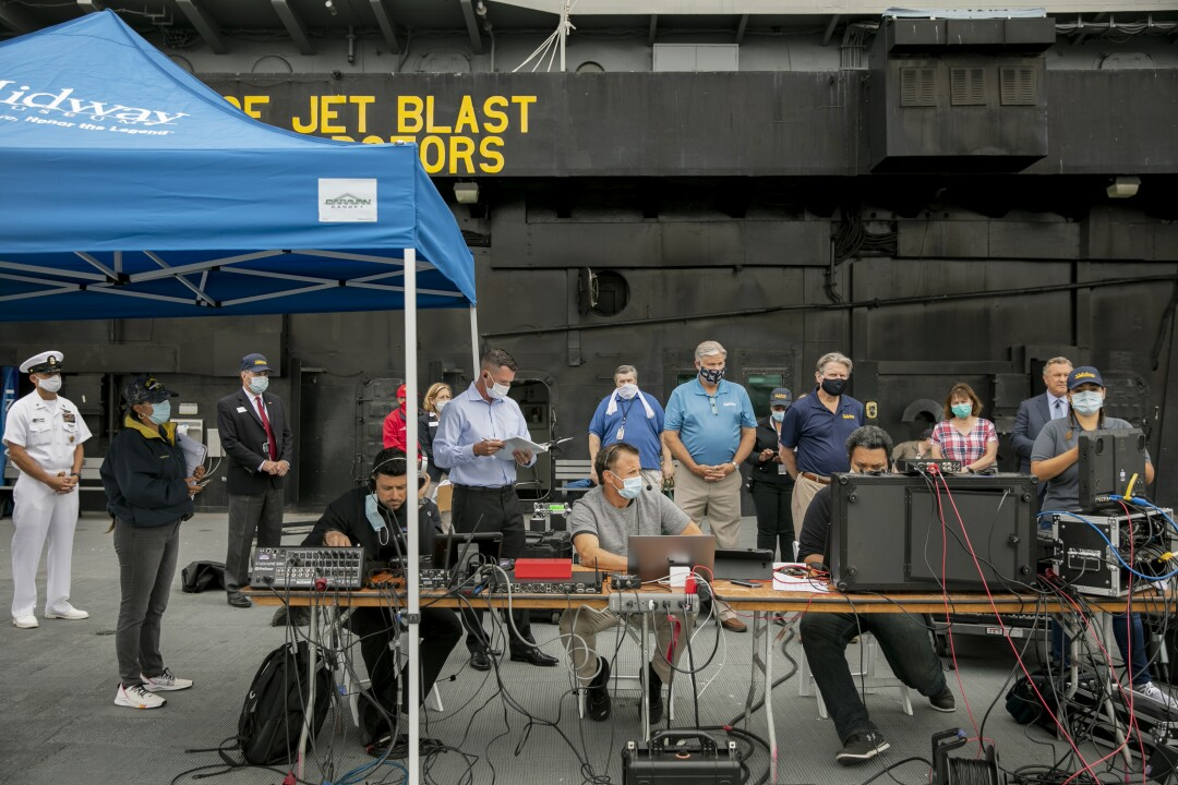 Production crew, staff and volunteers watch the live broadcast from around the county during a Memorial Day service aboard the USS Midway Museum.