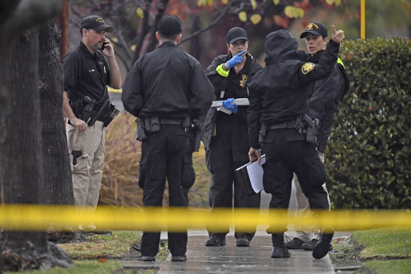 """In this photo taken Sunday, Dec. 1, 2019, police officers investigate the scene of an officer-involved shooting in Concord, Calif. Police in Northern California say Concord police officers shot and killed a 60-year-old man after he allegedly attacked his elderly parents. KPIX-TV reports the shooting Sunday in Concord happened after an older couple, aged 85 and 90, called police and said their son was acting """"erratically"""" and was possible under the influence of drugs and alcohol. (Jose Carlos Fajardo/Bay Area News Group via AP)"""