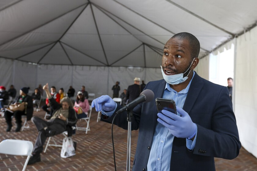 Kevin Ezeh, protected with face mask and gloves, addresses Tuesday's Los Angeles City Council meeting standing under a tent erected outside City Hall amid the threats of the coronavirus.
