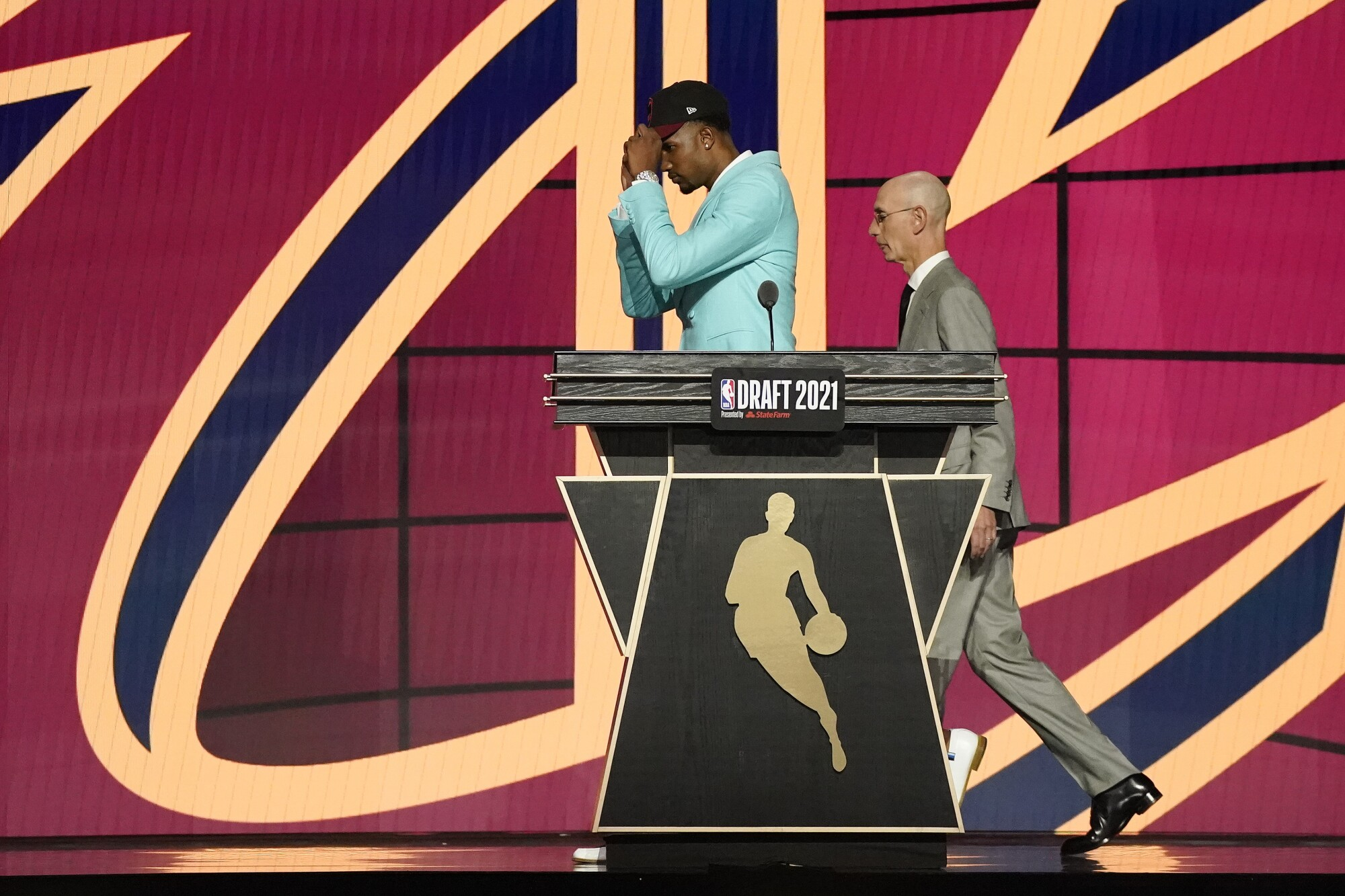 Evan Mobley walks off stage with NBA commissioner Adam Silver after being selected third overall by Cleveland on Thursday.