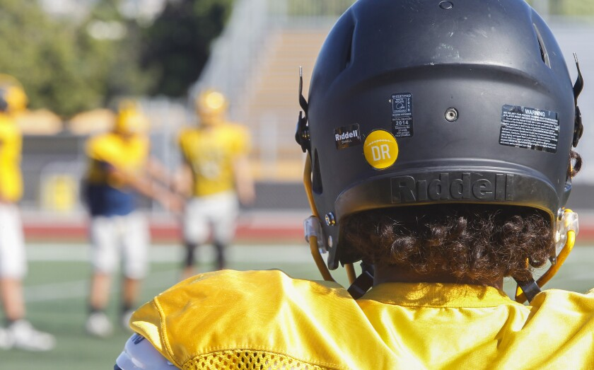 Mission Bay players are wearing decals on their helmets in memory of coach Dane Roman, who died in July.