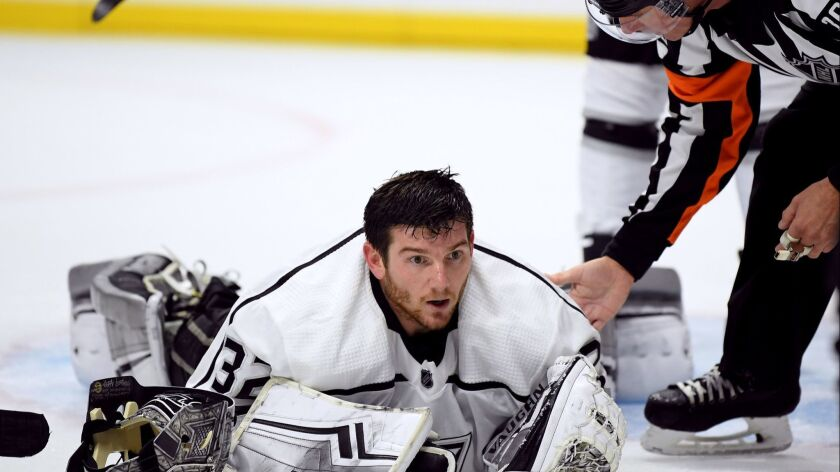 Kings goalie Jonathan Quick is checked on by referee Brian Pochmara after losing his face mask during the third period in a 2-0 win over the Carolina Hurricanes at Staples Center on Sunday.