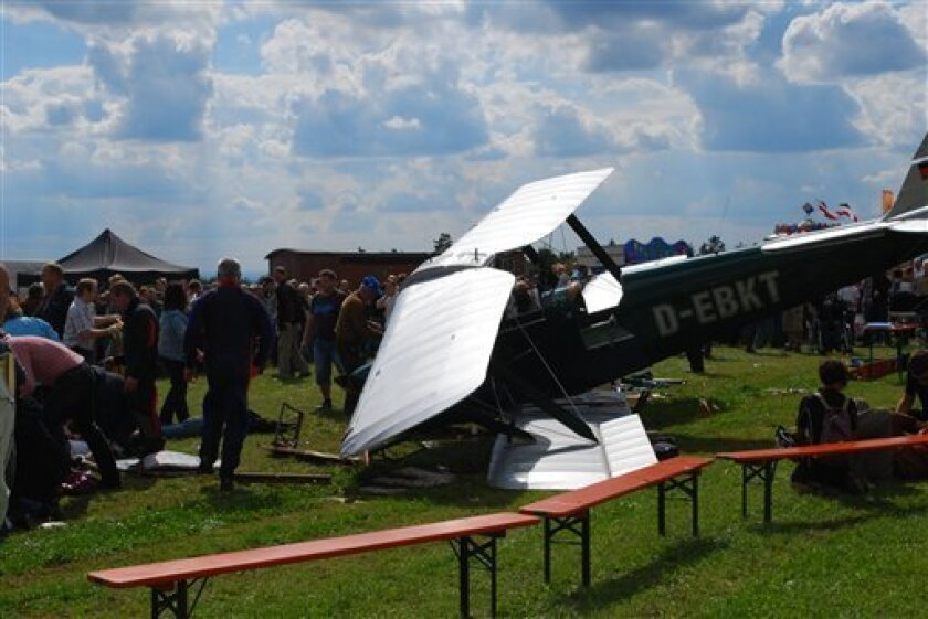 People stand next to the debris of a small plane at the Lillinghof airfield near the Bavarian town of Lauf Germany Sunday Sept. 5, 2010. Police say the pilot of the small propeller-driven plane lost control of his aircraft while taking part at a flight show in southern Germany and crashed into a group of spectators, leaving one person dead and several injured. A spokesman said Sunday that police had not yet established how many people were injured in the crash, at the Lillinghof airfield. (AP Photo/dapd/Stefanie Buchner-Freiberger)