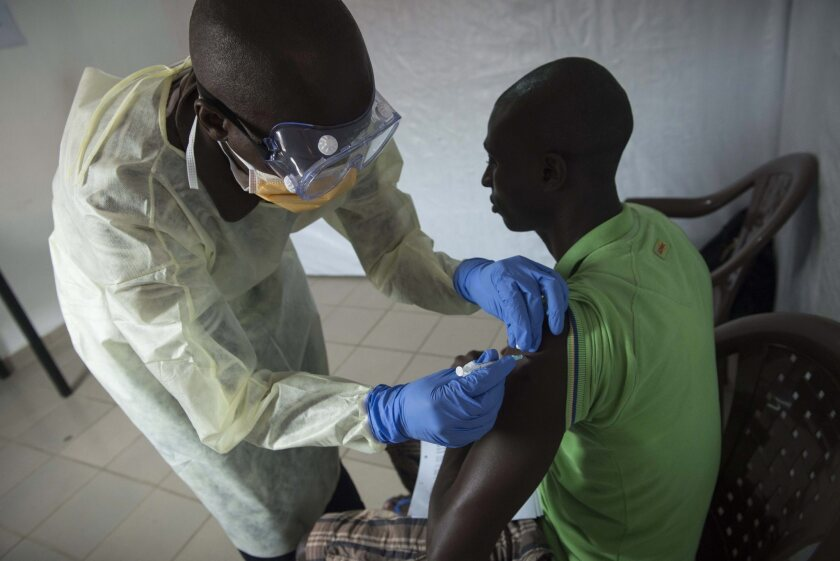 """A man receives the rVSV-ZEBOV vaccine against Ebola inside the Donka Hospital compound in Conakry, Guinea, on July 31, 2015. The medical journal The Lancet reported that results from a Phase III trial of the vaccine indicated it was """"highly effective"""" against Ebola."""