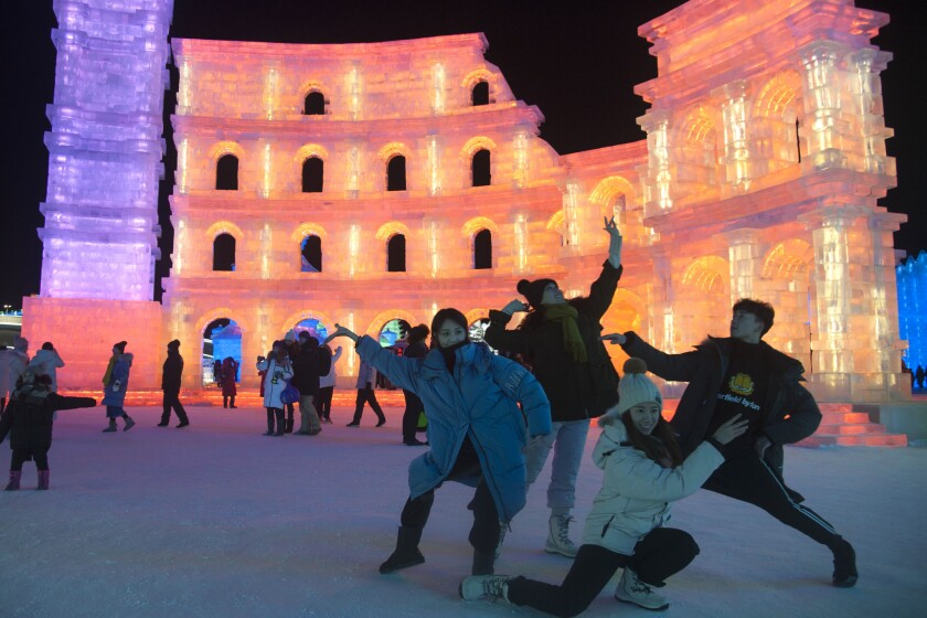 Tourists visit illuminated ice sculptures at Ice and Snow World park.