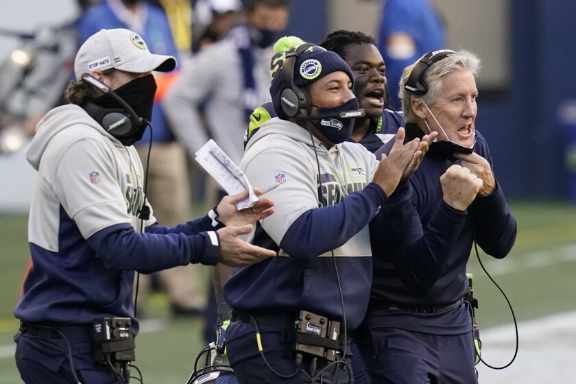 Seattle Seahawks head coach Pete Carroll, right, reacts with running back DeeJay Dallas, second from right, and other coaches after a play against the San Francisco 49ers during the second half of an NFL football game, Sunday, Nov. 1, 2020, in Seattle. (AP Photo/Elaine Thompson)