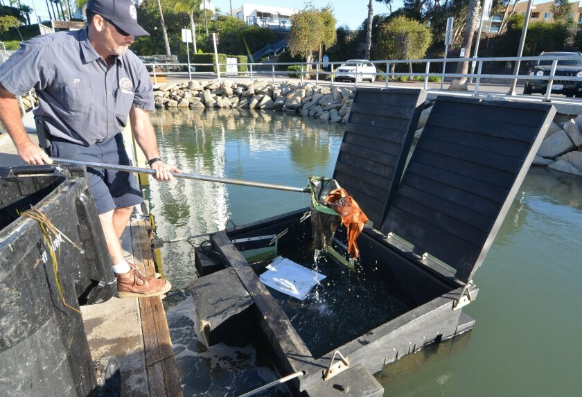 Oceanside Harbor maintenance worker Jon Perkins scoops trash out of one of the city's new skimmers on Friday morning. The city recently purchased two of the devices, which help remove debris from the water.