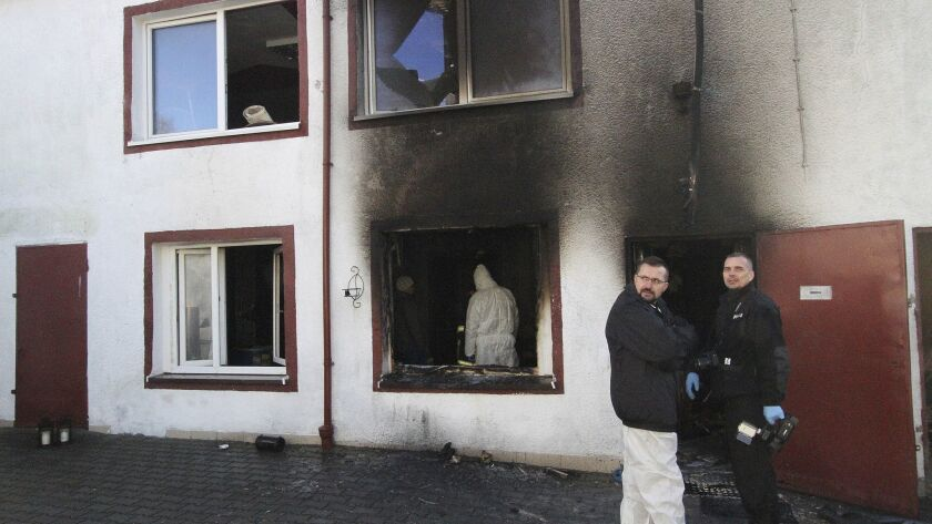 """Officials examine the site of an """"escape room"""" fire that killed five girls Friday in Koszalin, northern Poland."""