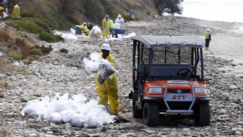 Workers load debris from cleanup efforts at Refugio State Beach on Thursday, June 4, 2015.