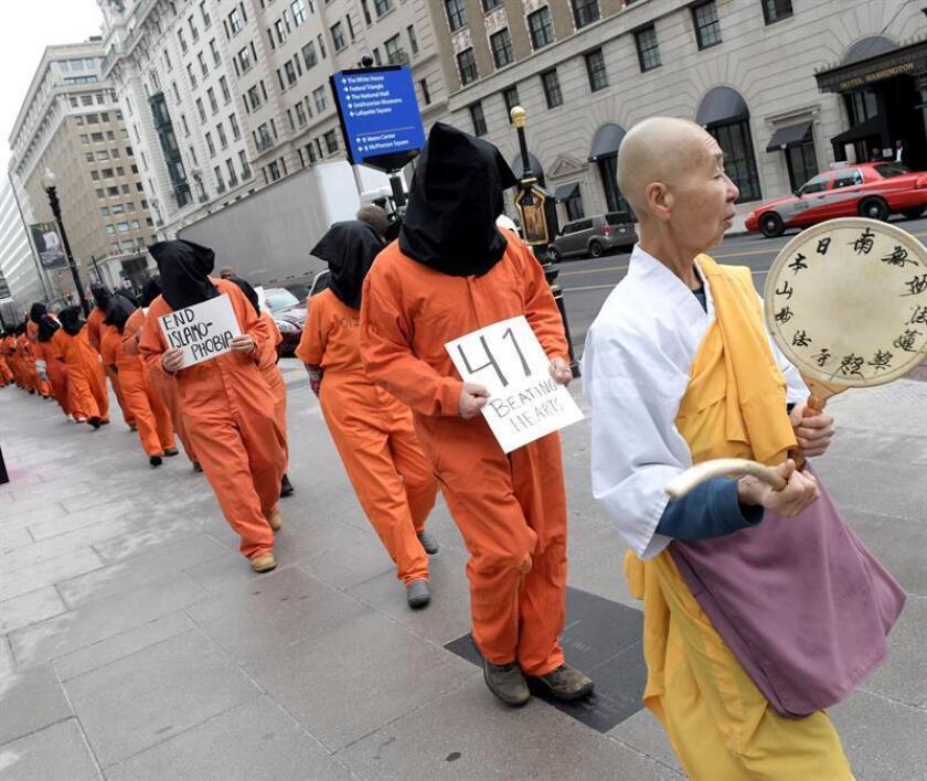 Un monje asiático camina delante de personas con la cabeza tapada y vestidas con ropas naranjas de los prisioneros de la cárcel de máxima seguridad, se manifiestan hoy, jueves 11 de enero de 2018, frente a la Casa Blanca en Washington (EE.UU.). EFE