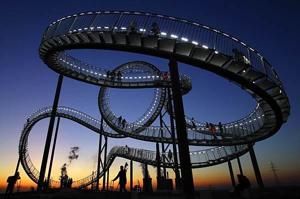 """""""Tiger and Turtle"""" rises 68 feet high. Its base is 158 by 113 feet. The """"track"""" stretches 722 feet and is about three feet wide."""