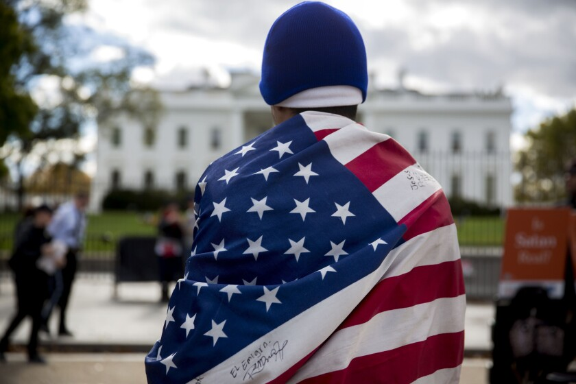 Jose Cruz wears a U.S. flag during a demonstration in favor of immigration reform outside of the White House in Washington, D.C.