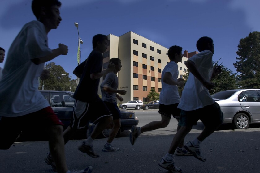 A group of athletes run past Mary Park Hall at San Francisco State University.