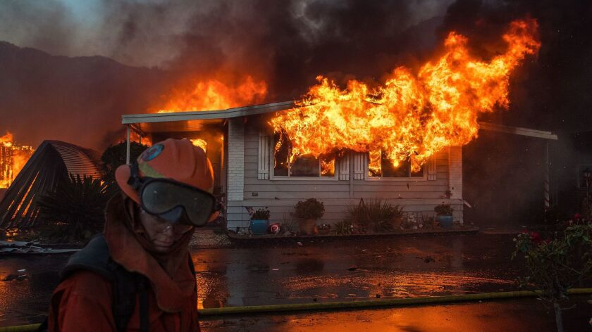 A firefighter turns away from the heat as flames explode through the front windows of a home burning in the Lilac fire in northern San Diego County.