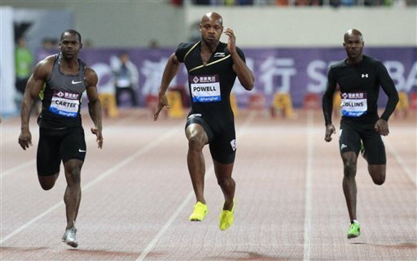 FILE - In this Saturday, May 19, 2013 file photo, Asafa Powell of Jamaica, center, competes with Nesta Carter of Jamaica, left, and Kim Collins of Saint Kitts, right, during the men's 100 meter at the Diamond League track and field competition in Shanghai, China. Former 100-meter world-record holder Asafa Powell and Jamaican teammate Sherone Simpson have each tested positive for banned stimulants, according to their agent. Paul Doyle told The Associated Press on Sunday, July 14, 2013 that they