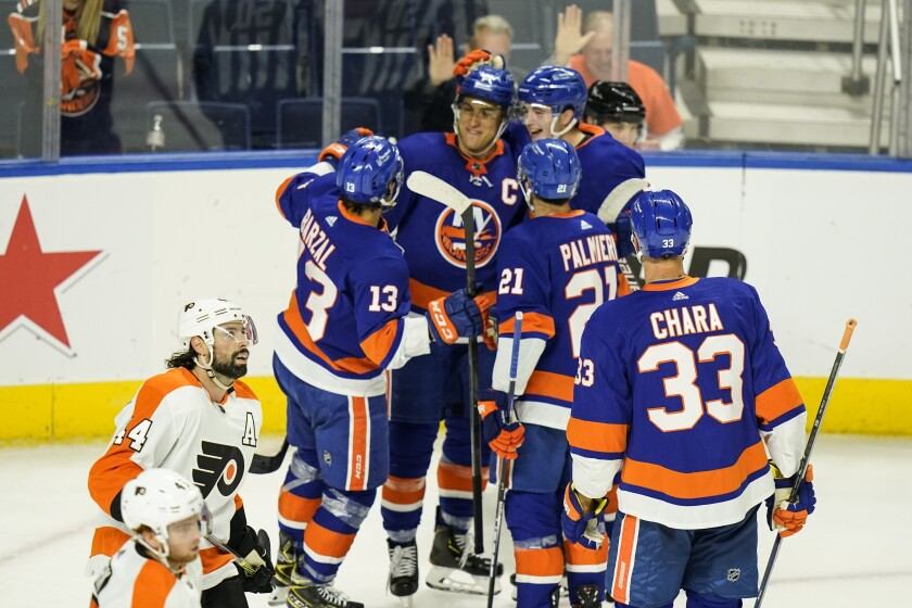 Philadelphia Flyers' Nate Thomposon skates past New York Islanders' Anders Lee as he celebrates with teammates after scoring a goal during the first period of a NHL preseason hockey game Tuesday, Oct. 5, 2021, in Bridgeport, Conn. (AP Photo/Frank Franklin II)