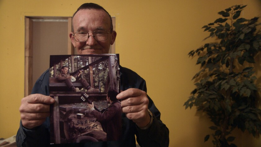 Actor Billy Redden poses with photos from his acting debut in the 1970's film Deliverance. Holler