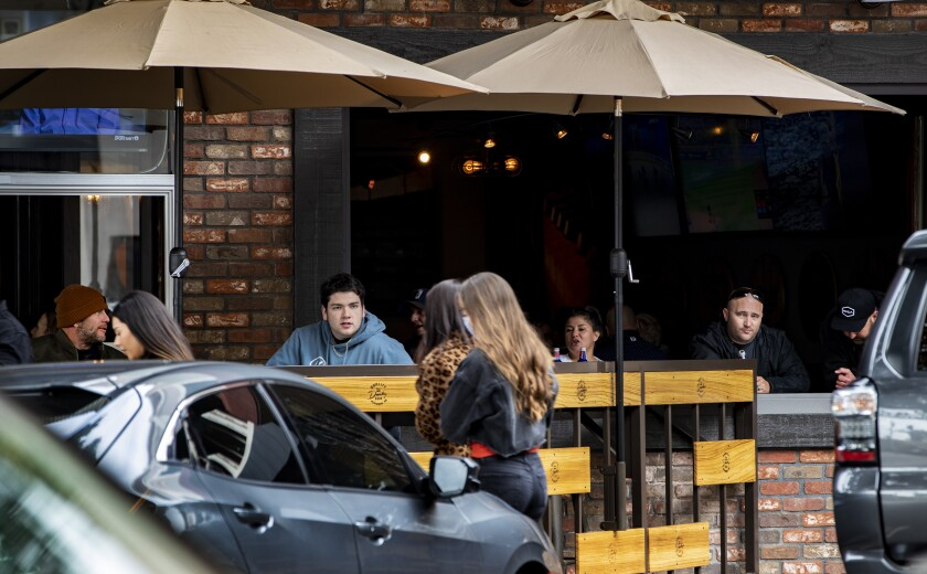 Customers fill the outdoor seating at a restaurant