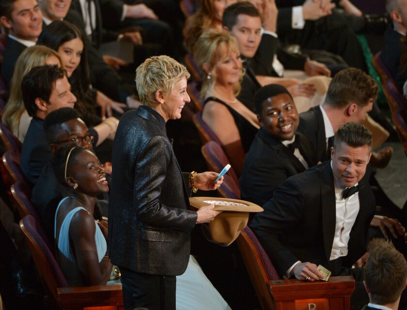 Lupita Nyong'o, left, laughs after handing Oscar host Ellen DeGeneres her lip balm to go toward the evening's pizza tip.