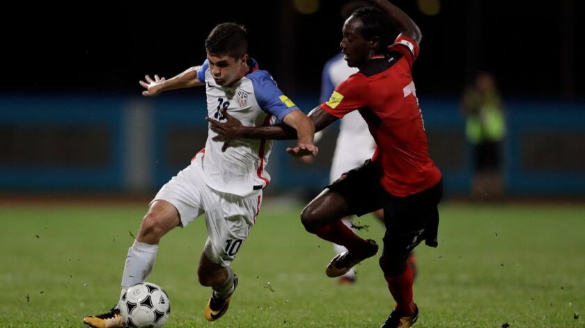United States' Christian Pulisic, left, fights for the ball with Trinidad and Tobago's Nathan Lewis during a 2018 World Cup qualifying soccer match in Couva, Trinidad.