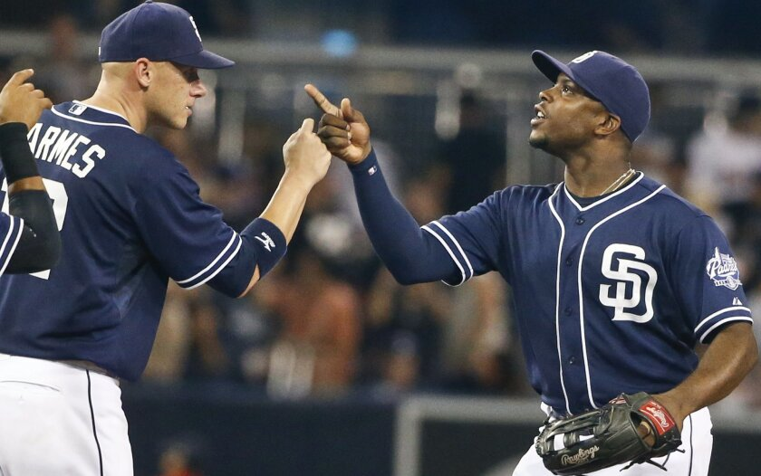 San Diego Padres' Justin Upton, right, congratulates Clint Barmes after the Padres' 5-4 victory over the Colorado Rockies in a baseball game Saturday, July 18, 2015, in San Diego. Barmes hit a two-run home run during the seventh inning. (AP Photo/Lenny Ignelzi)