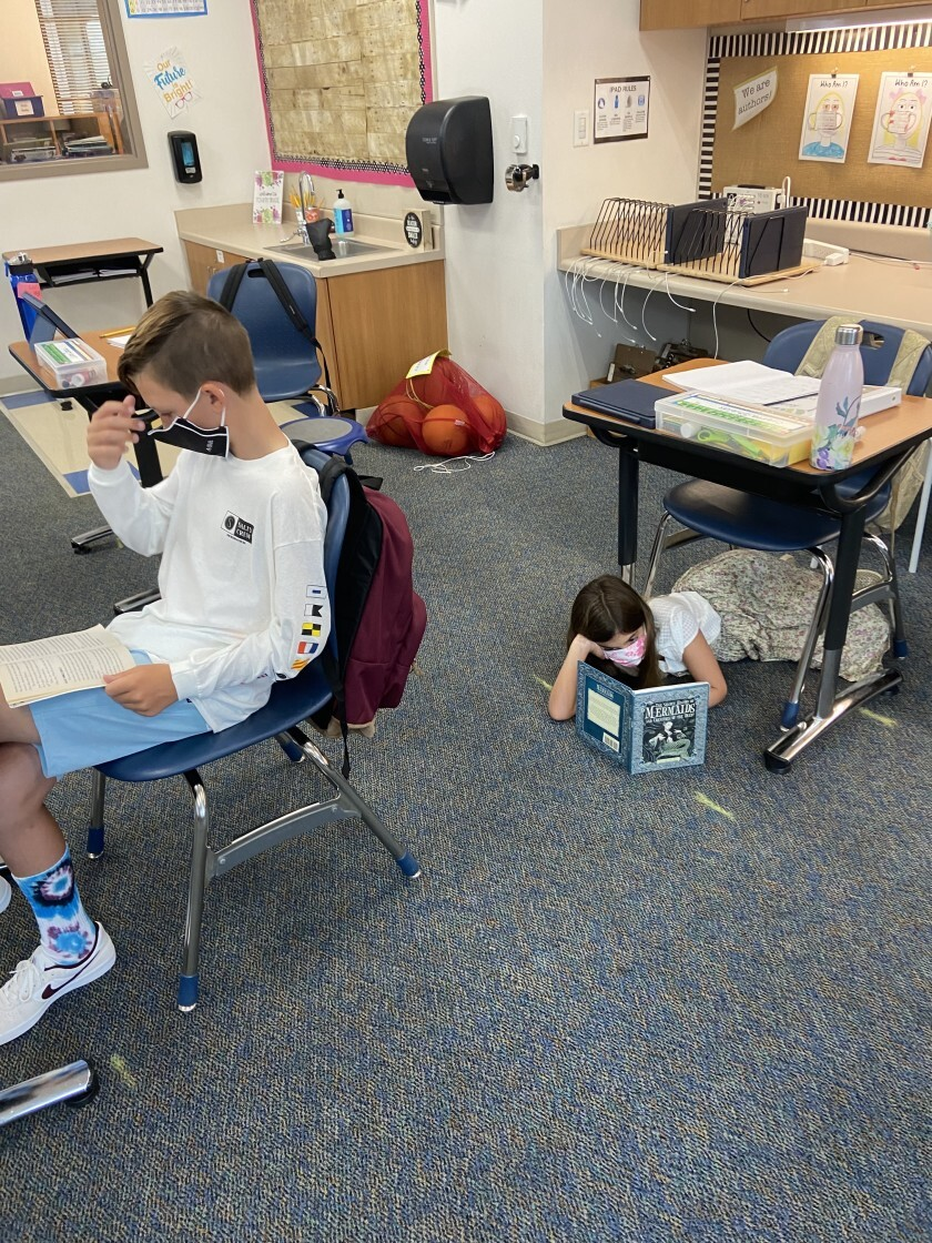 Students wear masks and keep six feet apart in the classroom.