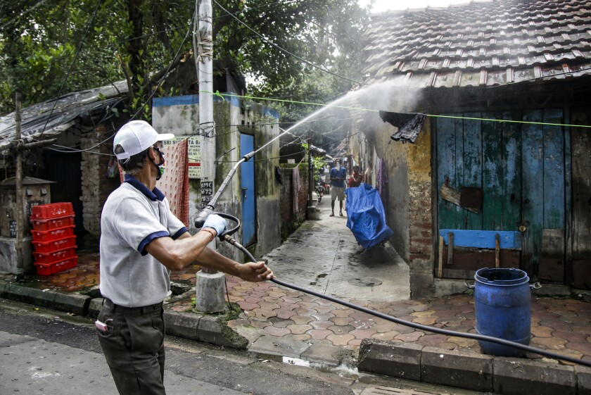 A civic worker disinfects an area inside a containment zone to prevent the spread of the coronavirus in Kolkata, India, Tuesday, July 14, 2020. Several Indian states imposed weekend curfews and locked down high-risk areas as the number of coronavirus cases surged past 900,000 on Tuesday. (AP Photo/Bikas Das)
