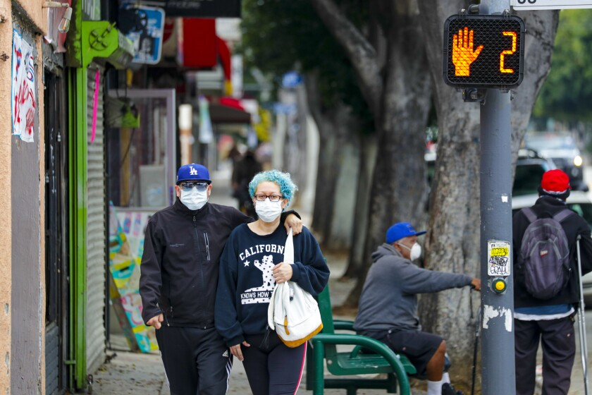 A couple in masks walk down Cesar E. Chavez Boulevard near downtown Los Angeles.