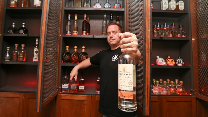 Frank Miller shows off some of the tequila collection at The Blind Burro in San Diego, where the tequila prices can change every five minutes based on demand.
