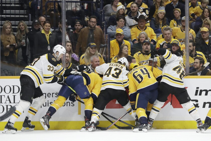 A group of Boston Bruins and Nashville Predators battle for the puck trapped against the boards in the second period of an NHL hockey game Tuesday, Jan. 7, 2020, in Nashville, Tenn. (AP Photo/Mark Humphrey)