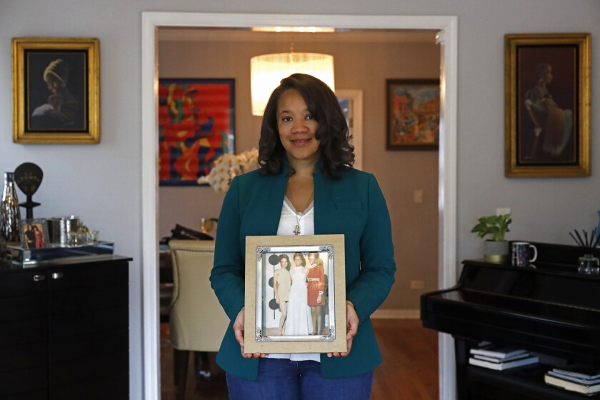Robin Rue Simmons, alderwoman of Evanston's 5th Ward poses for a portrait holding a photograph of her mother, aunt and grandmother in her home in Evanston, Ill., Friday, April 9, 2021. The Chicago suburb is preparing to pay reparations in the form of housing grants to Black residents who experienced housing discrimination. Simmons, a fourth generation Black resident, spearheaded the effort after studying racial disparity data, which shows the average income of Black families in Evanston is $46,000 less than that of white families. (AP Photo/Shafkat Anowar)