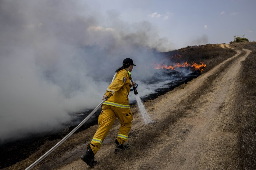 An Israeli firefighter helps extinguish a fire caused by incendiary balloons launched from the Gaza Strip on Wednesday.