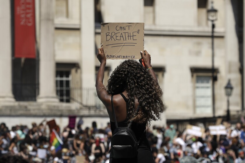 A woman holds up a sign as people gather in Trafalgar Square in London.