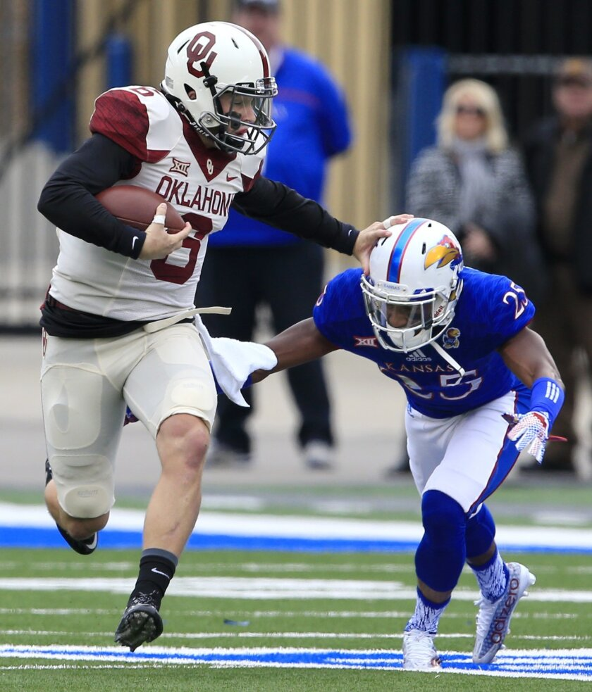 Oklahoma quarterback Baker Mayfield (6) stiff arms Kansas cornerback Marnez Ogletree (25) during the first half of an NCAA college football game in Lawrence, Kan., Saturday, Oct. 31, 2015. (AP Photo/Orlin Wagner)