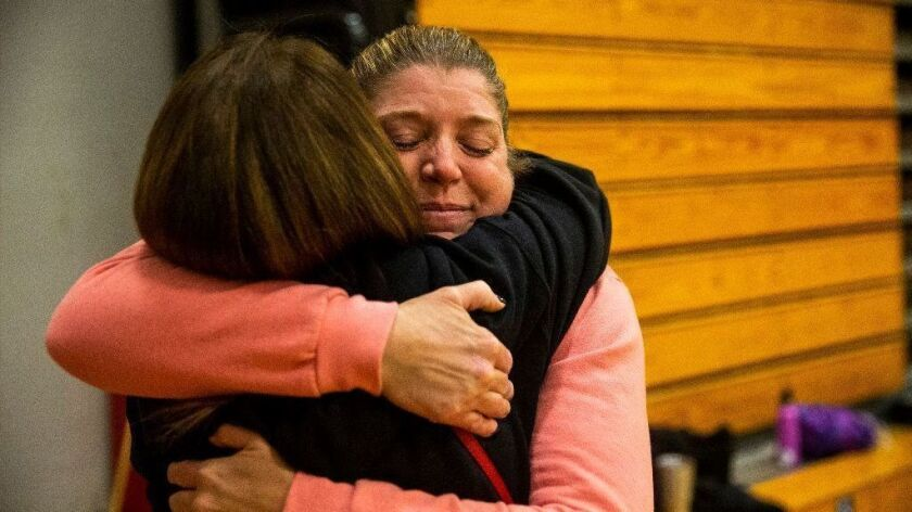 Displaced by the Camp fire, coach Sheila Craft gets a hug as the Paradise High School Bobcats hold practice at the Chico High School gymnasium on Nov. 15.